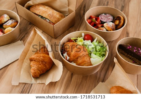 Different takeout food on wooden kitchen table. Italian panini sandwich, french croissant with salmon, strawberry pancakes and chocolate cheesecake. Close up, top view, pov, copy space, background. Royalty-Free Stock Photo #1718531713