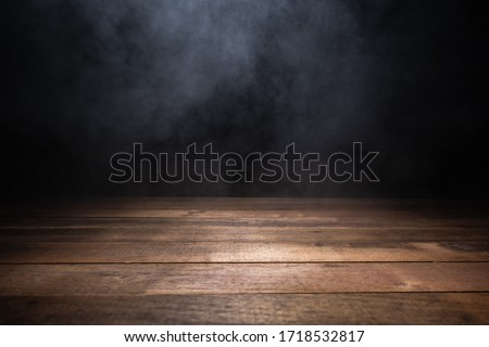 empty wooden table with smoke float up on dark background Royalty-Free Stock Photo #1718532817