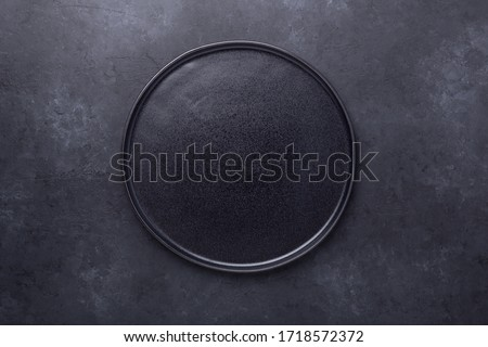 Empty ceramic plate on dark stone background Copy space Top view - Image Royalty-Free Stock Photo #1718572372