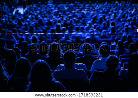 The audience in the cinema, the view from the back. Group of people at the business conference, back view, blue tones Royalty-Free Stock Photo #1718593231