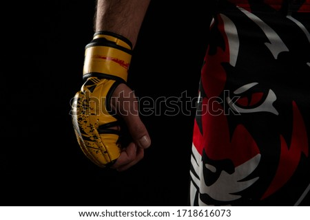 Mixed martial arts (MMA) fighter. Detail of the yellow glove with tiger pants on black background. Mixed martial arts concept. #1718616073