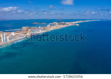 "Aerial drone photo of The Sandbar of the Minor Sea, ""La Manga"" in Spain which is a tiny strip in the middle of the sea with resorts and a beautiful skyline"