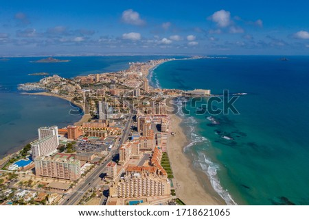"""Aerial drone photo of The Sandbar of the Minor Sea, """"La Manga"""" in Spain which is a tiny strip in the middle of the sea with resorts and a beautiful skyline"""