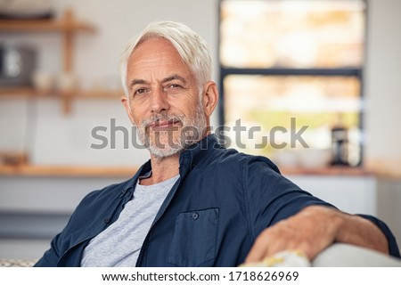 Handsome senior man with white hair sitting on couch and looking at camera. Satisfied old man relaxing on sofa while looking at camera. Portrait of proud mature man stay at home with copy space. Royalty-Free Stock Photo #1718626969