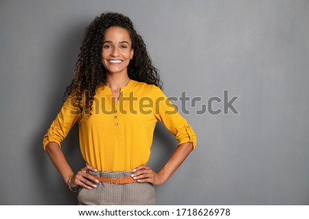 Portrait of young african woman standing with hands on waist and looking at camera. Confident stylish girl standing against grey background. Happy young mixed race woman smiling i with copy space. Royalty-Free Stock Photo #1718626978