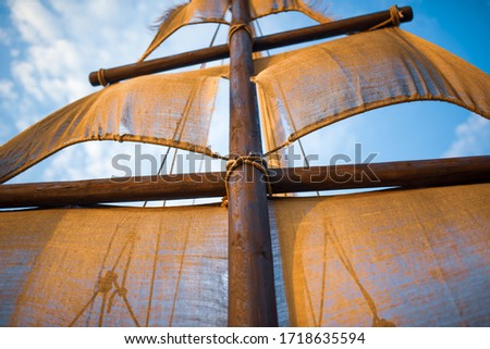 Bottom view of a ship mast with beige sails swings against a blue sky with sunny sunny summer warm day clouds. Marine and adventure concept Royalty-Free Stock Photo #1718635594