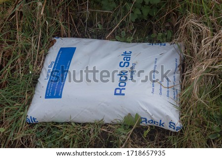 Large Plastic Bag of Rock Salt for Deicing a Road in Cold Weather and Snow in a Roadside Verge in Rural Devon, England, UK #1718657935