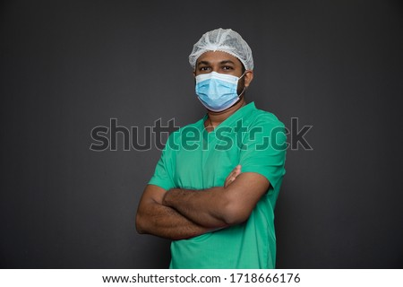 Portrait of a male nurse standing with arms folded isolated on a black background. Asian Nurse looking at camera. Male nurse with protective face mask against corona virus epidemic COVID-19 #1718666176