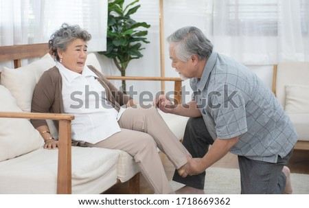 Senior elder asian man help his wife to sit on coach after fall down and get injury on leg or ankle in living at home. #1718669362