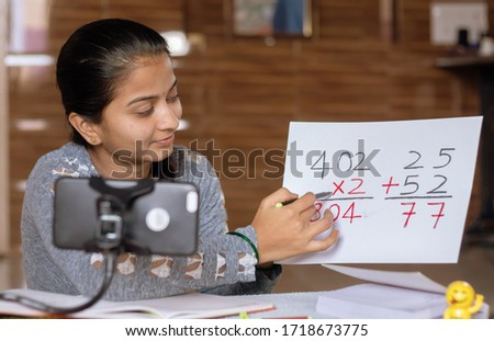 Girl taking online virtual class on mobile phone, busy in teaching at home during covid-19 or coronavirus pandemic crisis - Concept of e-teaching, online education or self isolation Royalty-Free Stock Photo #1718673775