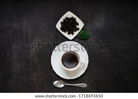 Close-up of a hot cup of coffee and coffee beans on old kitchen table. Top view with copyspace for your text.