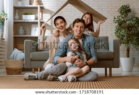 Mother, father and children girls in the room with a symbol of roof. Concept of housing for young family.  #1718708191