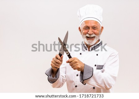Image of happy chef sharpens knives on gray background.