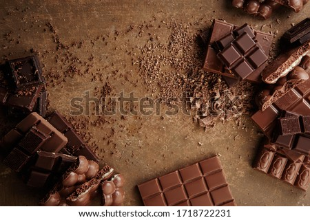 Composition of bars and pieces of different milk and dark chocolate, grated cocoa on a brown background top view close up #1718722231