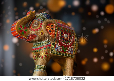 Colorful indian elephant sculpture on wood with bokeh background