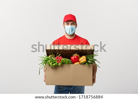 Delivery Concept: Handsome Caucasian grocery delivery courier man in red uniform and face mask with grocery box with fresh fruit and vegetable #1718756884