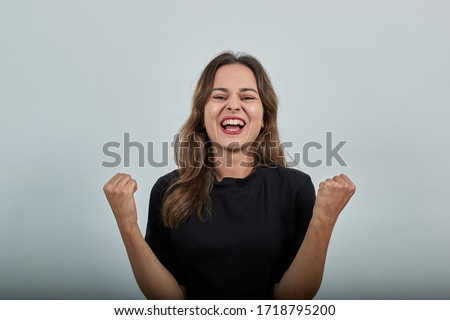 Cute Young Woman Brunette In Black T-Shirt, Blue Jeans With Belt On Gray Background, Happy Girl Smiles, Clenched Her Hands Into Fists And Raised Them Up Royalty-Free Stock Photo #1718795200
