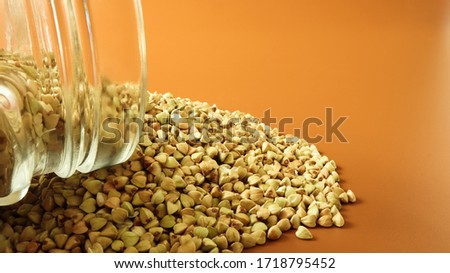 Scattered raw green buckwheat with a glass jar for cereals. Vegan organic food concept. The concept of diet, weight loss, healthy and proper nutrition. Triangle shaped scatter kernels #1718795452