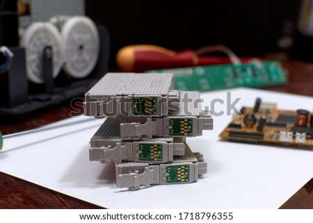 The printer is disassembled. Repair of the printer. Color ink cartridges for an inkjet printer. An inkjet printer motherboard. Maintenance of inkjet printers #1718796355