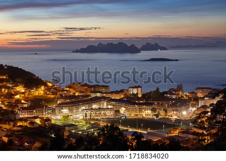 Sunset view of the city of Baiona with the silhouette in the background of the Cies islands in Galicia, Spain. #1718834020