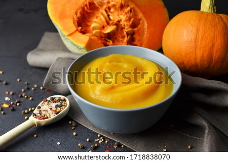 Pumpkin puree with fresh pumpkins and spices in spoon on linen cloth over dark grunge background Royalty-Free Stock Photo #1718838070