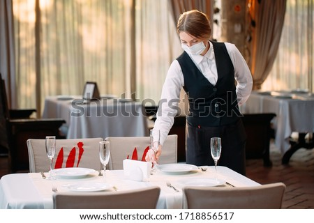 A waiter in a medical protective mask serves the table in the restaurant #1718856517