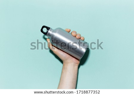 Close-up of male hand holding reusable, aluminum thermo bottle for water, on studio background of cyan, aqua menthe color. Zero waste. Plastic free. #1718877352