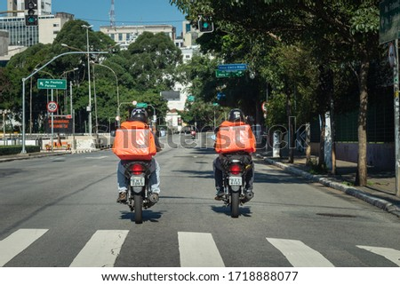 São Paulo, Brazil - april 5, 2020: An outbreak of a pandemic disease. No cars at street at all, only bikers delivering food and packages across the city. #1718888077