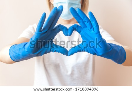Nurse doctor hands in blue medical gloves in the shape of heart against the background of her body. Close up. Blurred background. Thanks to health workers concept. Gratitude to the medical staff. #1718894896