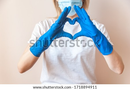 A female doctor in blue medical gloves, white T-shirt and blue medical mask on face makes a heart out of her hands. Thanks to health workers concept. Gratitude to the medical staff. #1718894911