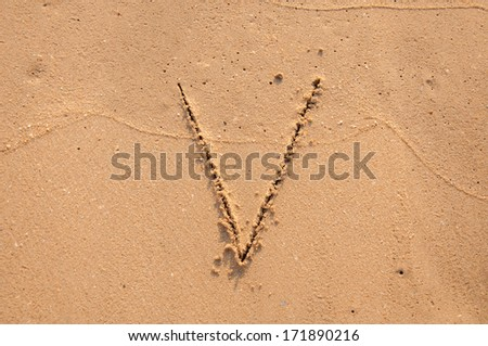 V text written in the sandy on the beach #171890216