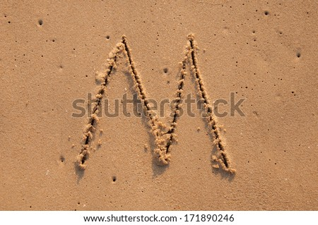M text written in the sandy on the beach #171890246