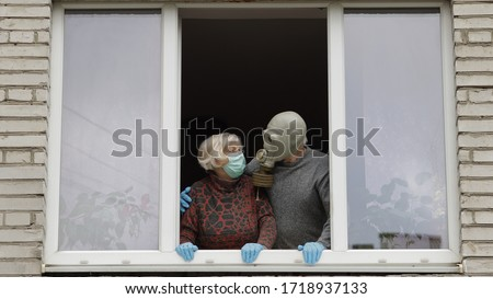 Old grandfather in gas mask and grandmother in protection mask stay at window. Isolated at home on quarantine. Virus outbreak. Elder man, woman. COVID-19 pandemic coronavirus. Social distancing #1718937133