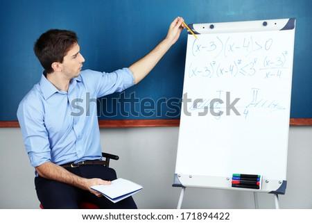 Young teacher sitting near chalkboard in school classroom #171894422