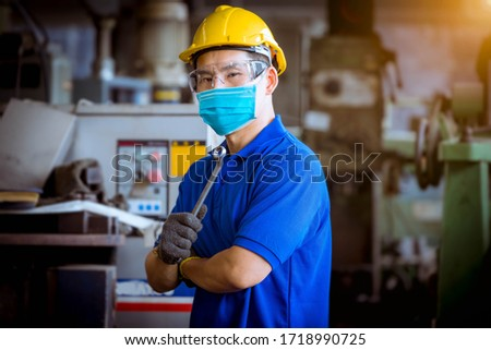 Portrait industry man worker standing and holding screwdriver for work on factory station by wearing safety mask to protect for pollution and virus in factory. #1718990725