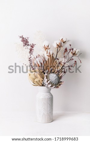 Beautiful dried flower arrangement in a stylish ceramic white vase. Dried flowers include pink proteas, banksia, gold palm leaf, kangaroo paw, cotton and ruscus leaves. Royalty-Free Stock Photo #1718999683