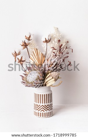 Beautiful dried flower arrangement in a stylish ceramic white vase with brown aztec pattern. Dried flowers include pink proteas, banksia, gold palm leaf, kangaroo paw, cotton and ruscus leaves. Royalty-Free Stock Photo #1718999785