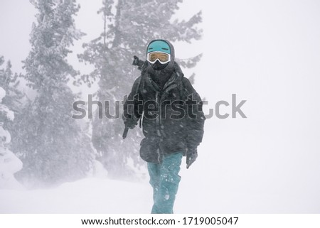 Camera man with tripod wearing snowboard mask  walking outdoor during strong blizzard