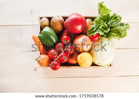 Fresh produce delivery box on wooden background. Food donaton box with copy space.  #1719038578