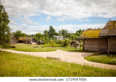 Summer sunny day in a russian village. The landscape depicts old wooden houses, trees and shrubs. Image with selective focus. Royalty-Free Stock Photo #1719097006
