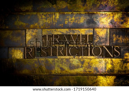 Photo of real authentic typeset letters forming Travel Restrictions text on vintage textured grunge copper and gold background