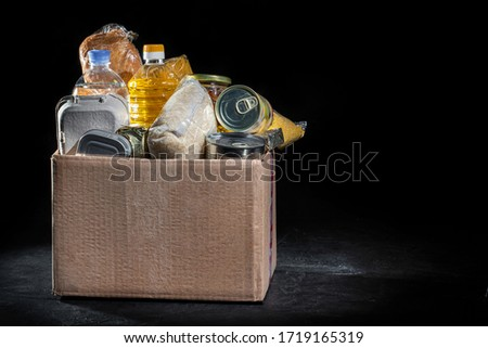 Donation box full of different products on dark background #1719165319