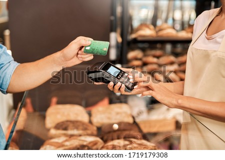 Young woman assistant wearing apron holding card machine inserting sum taking payment for purchase from customer at bakery shop small business close-up