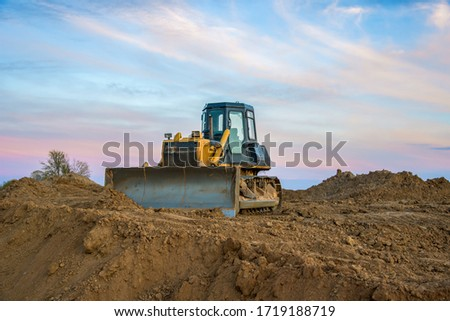 Dozer at open pit mining on sunseet background. Bulldozer for land clearing, grading, pool excavation, utility trenching and foundation digging. Earth-moving equipment. Small sharpness, granularity #1719188719