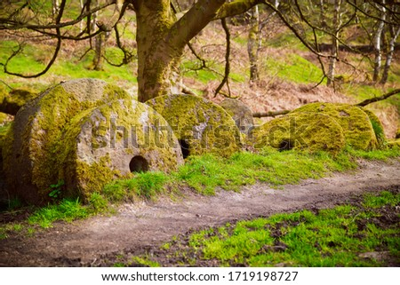 A group of millstones covered in moss lying by the footpath in the Peak District National Park, England, UK