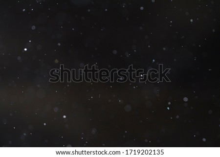 Detail of floating dust particles lit against a black background. Royalty-Free Stock Photo #1719202135