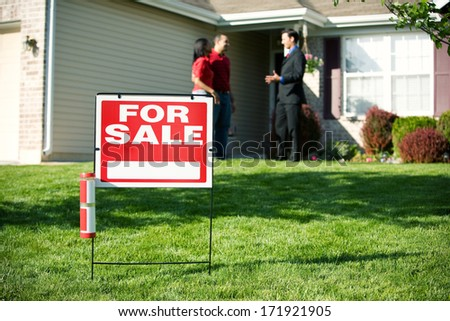 Real Estate: For Sale Sign With Agent And Home Buyer Behind