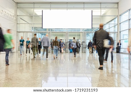 Blank luminous white banner over a trade fair or congress aisle with many people #1719231193