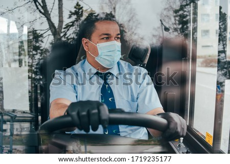 young hispanic man bus driver  in a protective mask and black gloves. prevent the spread of coronavirus. young hispanic bus driver wearing a protective mask and looks at road. quarantine. covid 19. #1719235177