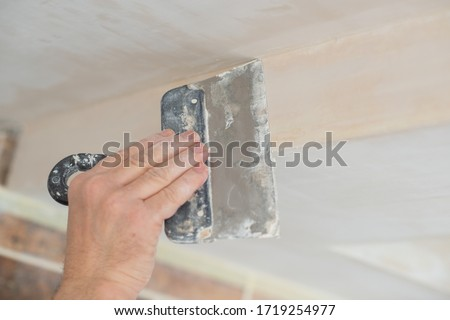 Worker putsty plasterboard ceiling in new building. Repairman works with plasterboard, plastering dry-stone wall, home improvement. A man makes repairs at home. Putty knife in male hand #1719254977